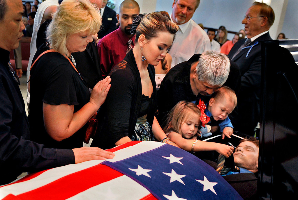 ". Chantel Blunk, center, says good-bye to her husband, Jonathan Blunk, surrounded by family and friends and her two children, Maximus Blunk, 2, and Hailey Blunk, 4, on Friday, August 3, 2012, during a full military funeral at Mountain View Mortuary in Reno, Nevada. The night before Blunk\'s funeral, Hailey was upset that her father wouldn\'t wake up as he lay in his coffin. ""You choke on the words, but you can only smile and try to explain it,\"" Blunk said."