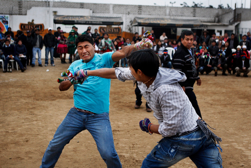. Eloy Luna, left, and Rony Garate fight during a Takanakuy ritual fight in Lima, Peru. When the brightly hued ski masks come off, the punching and kicking begin. Only once a judge has ruled one of the combatants licked do they stop fighting. (AP Photo/Karel Navarro)