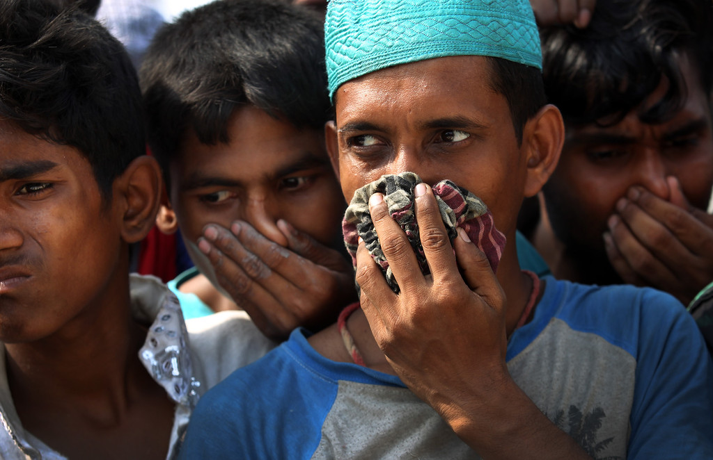 . People cover their noses to block out the smell of decomposing bodies as a truck transporting unclaimed bodies from the garment factory building that collapsed last week arrives for a mass burial, Wednesday, May 1, 2013, in Dhaka, Bangladesh.    (AP Photo/Wong Maye-E)