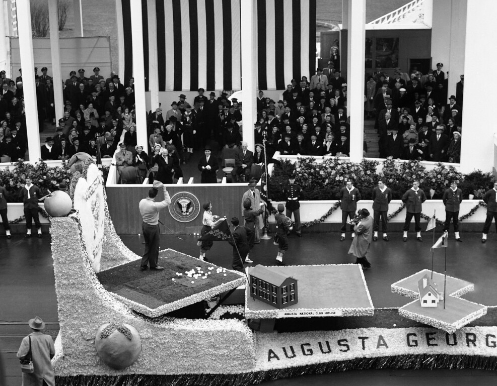 . President Dwight Eisenhower waved his hat and enjoyed himself thoroughly when member of the Georgia float hit several indoor practice golf balls toward him in the reviewing stand during inaugural parade in Washington on Jan. 21, 1957. Also enjoying the bit of by-play are Ike�s son, Maj. John Eisenhower, his wife, Barbara and Mamie. (AP Photo)