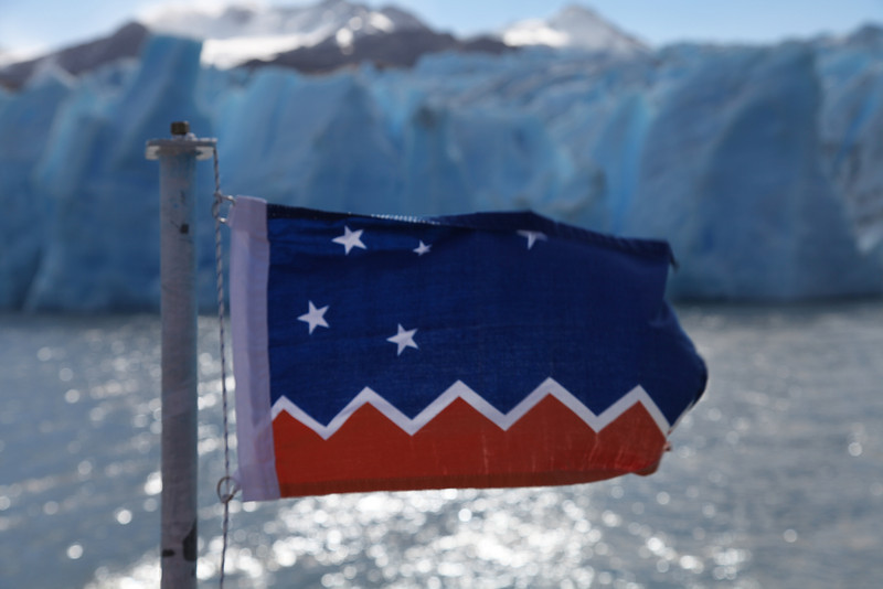 The flag of Providencia Magellanes, Patagonia, Chile. (Glaciar Grey in the background)