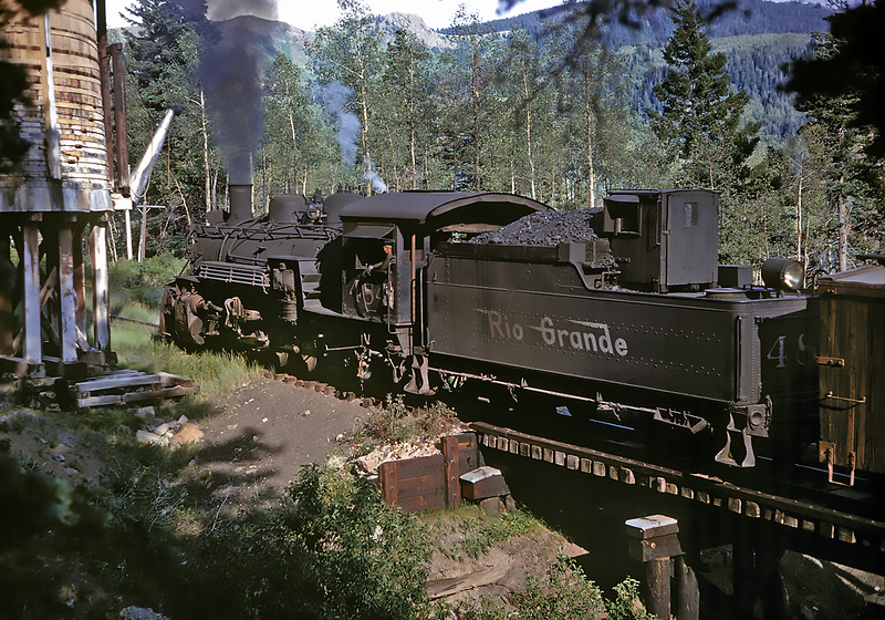 July 23, 1963.  Passing Cresco tank.  Trains rarely stopped here for water.  The fireman on this engine is Ed Trump, who was wearing his favorite green sweater.  Ed later became a lineman for the DRGW and maintained the telegraph and telephones lines along the narrow gauge in their last years.  The date of this picture is based on his time book.