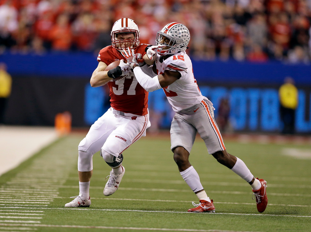 . Wisconsin\'s Garrett Groshek (37) is tackled by Ohio State\'s Denzel Ward during the second half of the Big Ten championship NCAA college football game, Saturday, Dec. 2, 2017, in Indianapolis. (AP Photo/AJ Mast)