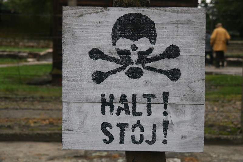 "After seeing an English word ""Halt"" on the signs, I did research to see if this was added to cater to tourists. Period film taken just after the camp liberation in 1945 showed this is real. The photos/video I found had the skull and crossbones on the side, not the top, but the words, size, and design were identical. The German language word for stop is actually ""halten"". Stoj means ""stand""."