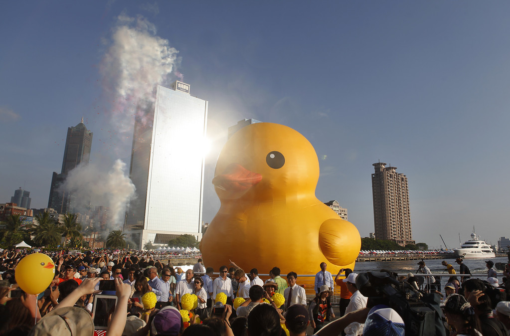 . People gather to see a giant Rubber Duck by Dutch conceptual artist Florentijin Hofman at Glory Pier on September 19, 2013 in Kaohsiung, Taiwan.  (Photo by Ashley Pon/Getty Images)