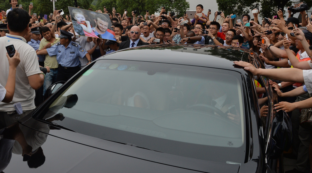 """. A huge crowd gathers around the car carrying football superstar David Beckham at Tonji University in Shanghai on June 20, 2013.  Football superstar David Beckham\'s visit to China turned \""""chaotic\"""" on Thursday after at least five people were hurt in a stampede as fans rushed to see him, local media and an AFP photographer at the scene said.  PETER PARKS/AFP/Getty Images"""