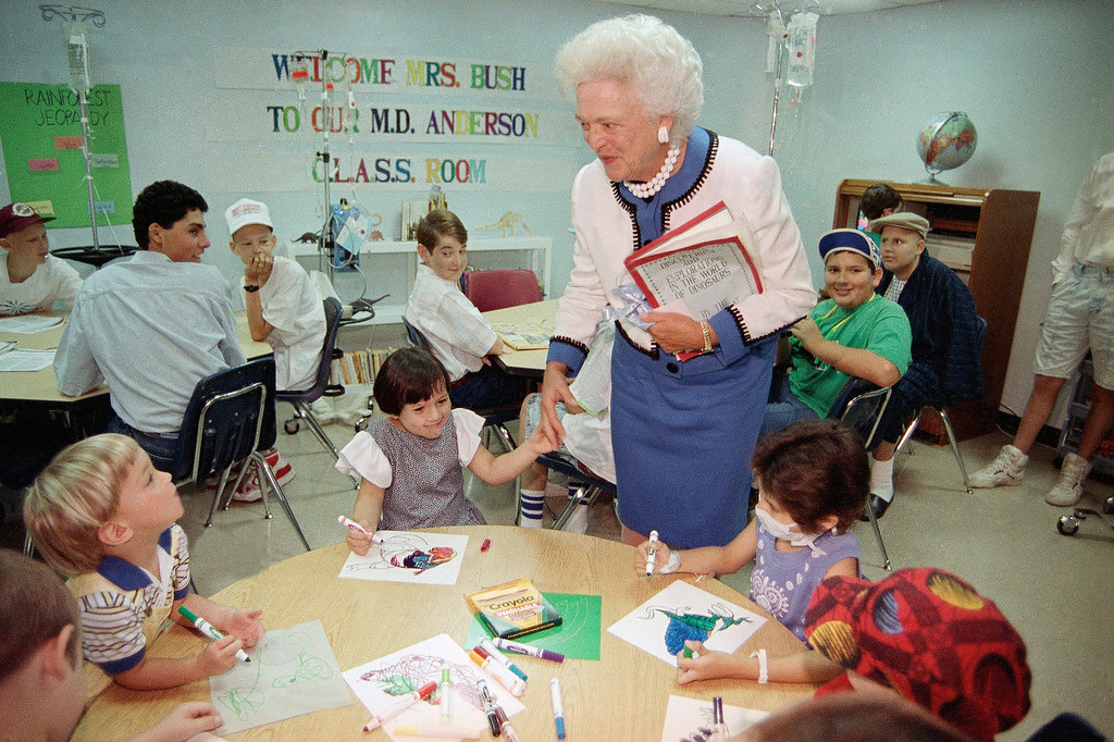 . First lady Barbara Bush holds hands with six-year-old Rachel Daly of Cypress, Texas, during a visit with cancer patients at the M.D. Anderson Hospital of the Texas Medical Center in Houston, July 11, 1990. Eight-year-old Christina Rodriguez of Edcouch, Texas wears a mask. (AP Photo/Greg Gibson)