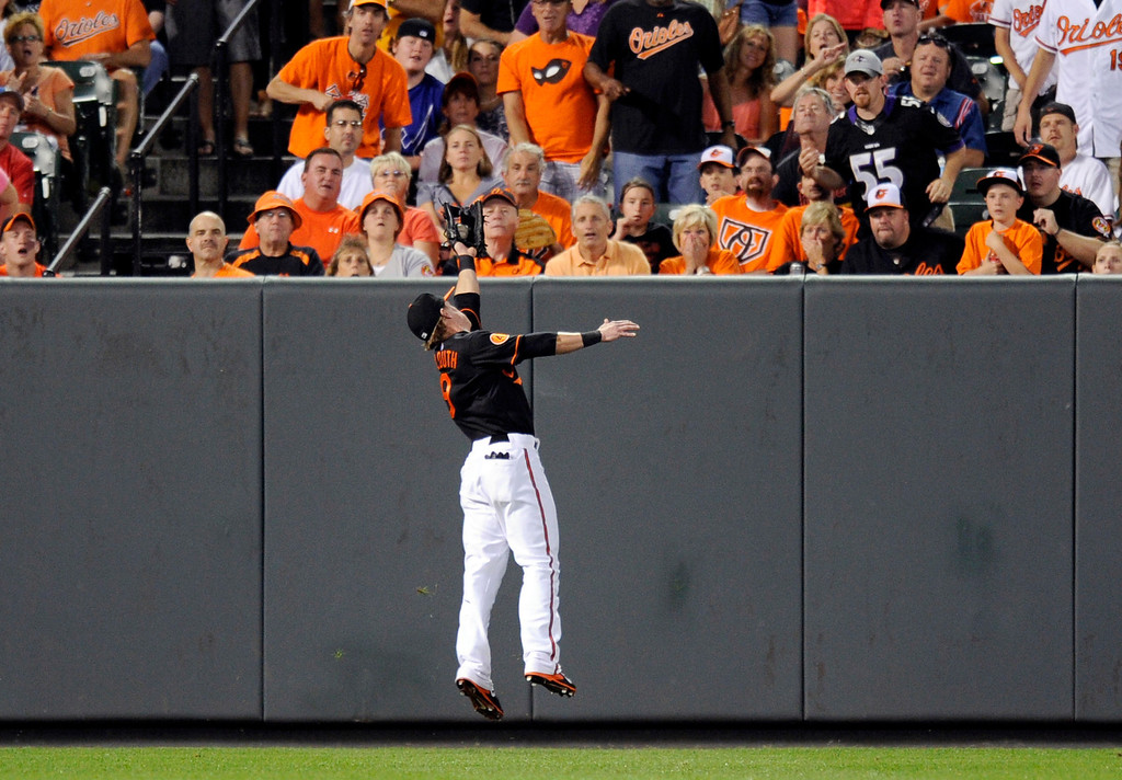 . Baltimore Orioles left fielder Nate McLouth makes a catch for the out on a liner by Colorado Rockies\' Todd Helton during the fifth inning of a baseball game, Friday, Aug. 16, 2013, in Baltimore. (AP Photo/Nick Wass)