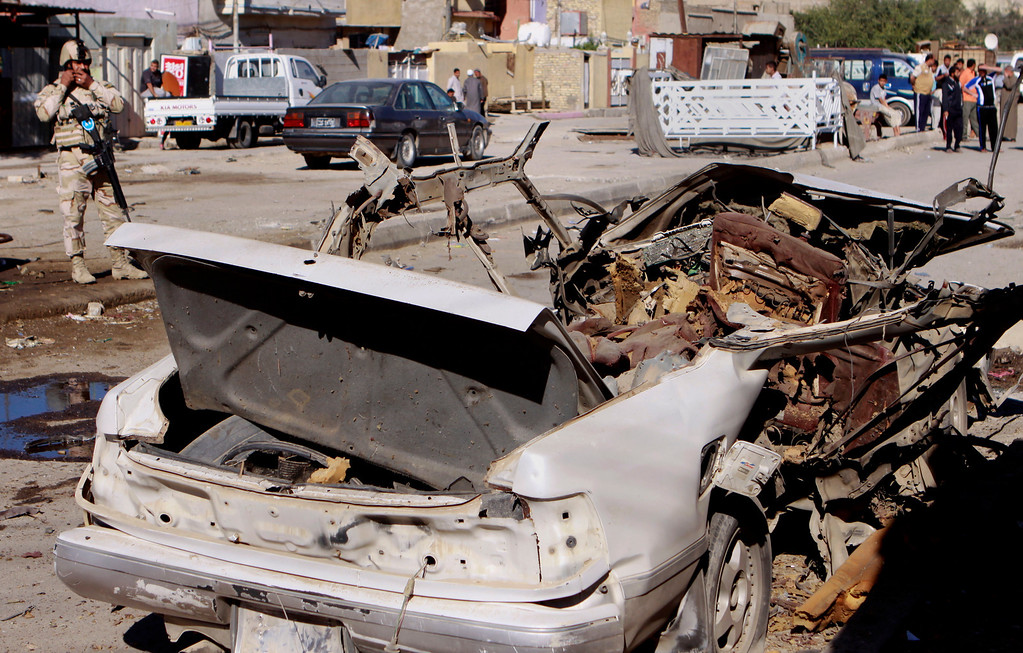 . A federal policeman stands guard at the scene of a car bomb attack in the Shiite stronghold of Sadr City, Baghdad, Iraq, Tuesday, March 19, 2013. (AP Photo/ Karim Kadim)