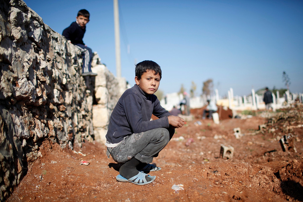 . A child watches men dig graves for future casualties of Syria\'s civil conflict at Sheikh Saeed cemetery in Azaz city, north of Aleppo December 30, 2012.    REUTERS/Ahmed Jadallah