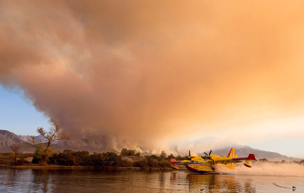 . Super Scooper firefighting aircraft skim water in the Santa Fe Dam Recreational Area in Irwindale, Calif. to fight the Colby Fire burning in the Angeles National Forest and Glendora, Calif. Jan. 16, 2014.  (Staff photo by Leo Jarzomb/San Gabriel Valley Tribune)