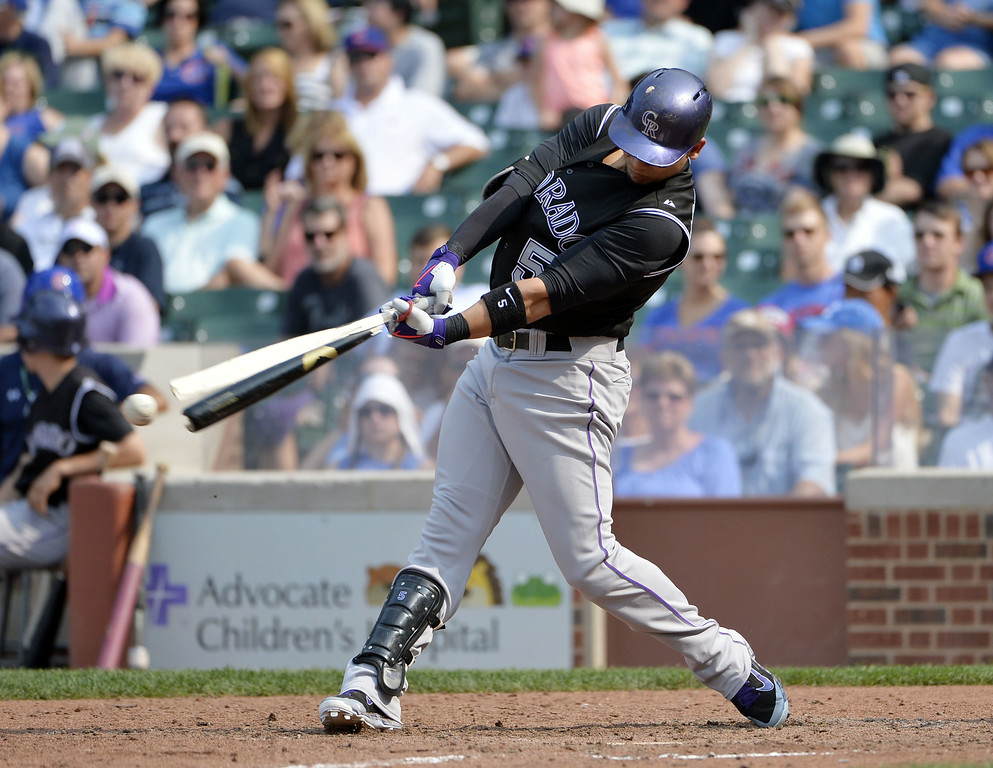 . Carlos Gonzalez #5 of the Colorado Rockies breaks his bat as he hits into a fielder\'s choice during the ninth inning against the Chicago Cubs at Wrigley Field on July 31, 2014 in Chicago, Illinois. The Cubs defeated the Rockies 3-1.  (Photo by Brian Kersey/Getty Images)