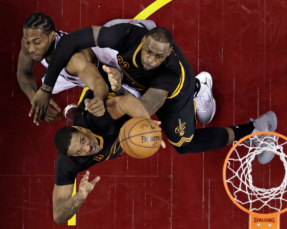 . Cleveland Cavaliers\' LeBron James, top right, blocks out San Antonio Spurs\' Kawhi Leonard, left, as Channing Frye shoots during the second half of an NBA basketball game, Saturday, Jan. 21, 2017, in Cleveland. The Spurs won 118-115 in overtime. (AP Photo/Tony Dejak)