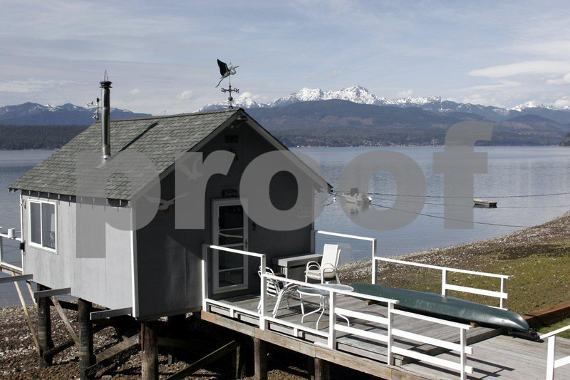 A small cabin on the shores of Hood Canal near Union, WA with the Olympic Mountains in the background.
