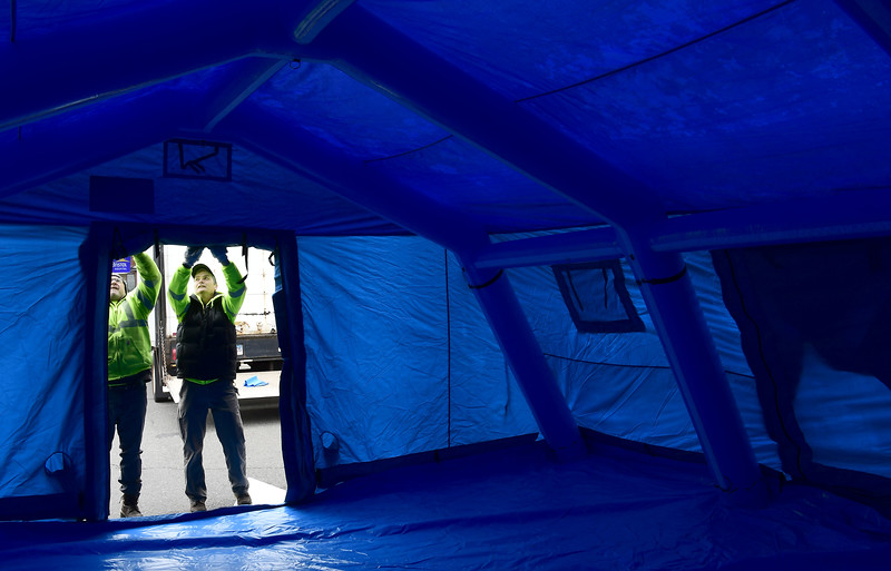 3/25/2020 Mike Orazzi | Staff Bristol Hospital employees Steve Oakes, and John Pardus while setting up a tent outside the emergency room entrance today that will be used to triage COVID-19 patients.