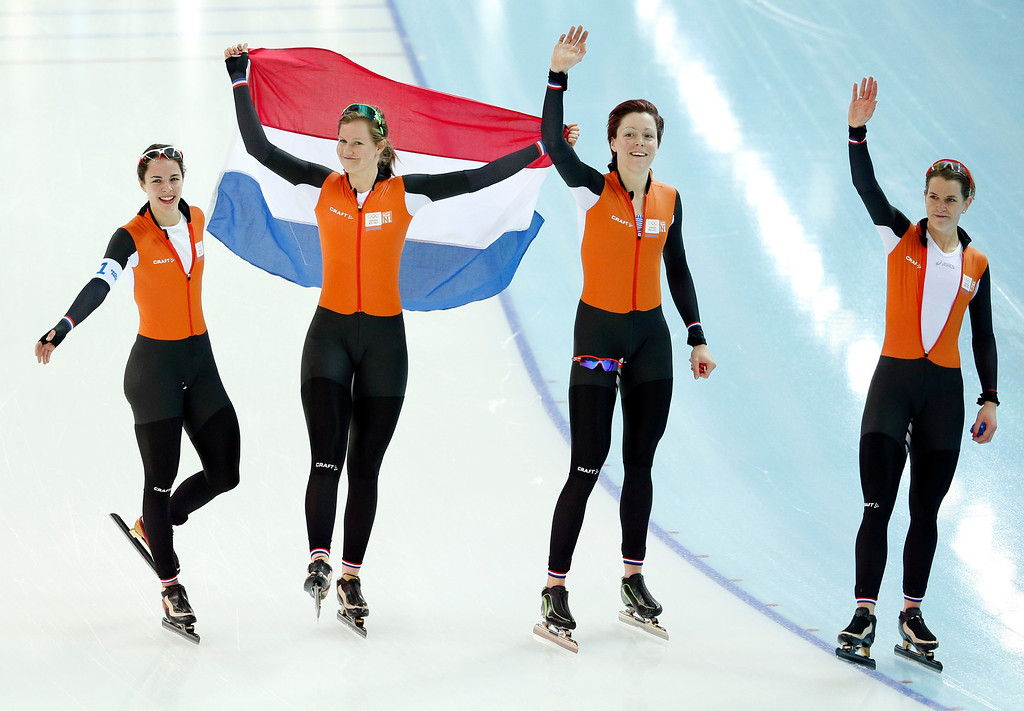 . Marrit Leenstra, Lotte van Beek, Jorien ter Mors, and Ireen Wust of the Netherlands celebrate with the national flag after taking the gold medal on the women\'s team pursuit at the Adler Arena Skating Center at the 2014 Winter Olympics, Saturday, Feb. 22, 2014, in Sochi, Russia. (AP Photo/Pavel Golovkin)