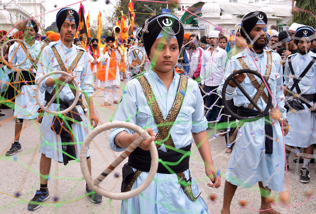 . Sikh youths demonstrate Gatka martial arts skills during a procession to mark \'Hola Mohalla\' at the Golden Temple in Amritsar on March 17, 2014. Hola Mohalla is a three day Sikh festival, in which Nihang Sikh \'warriors\' perform Gatka (mock encounters with real weapons), tent pegging and bareback horse-riding, which usually falls in March following the Hindu festival of Holi. AFP PHOTO / NARINDER NANU/AFP/Getty Images