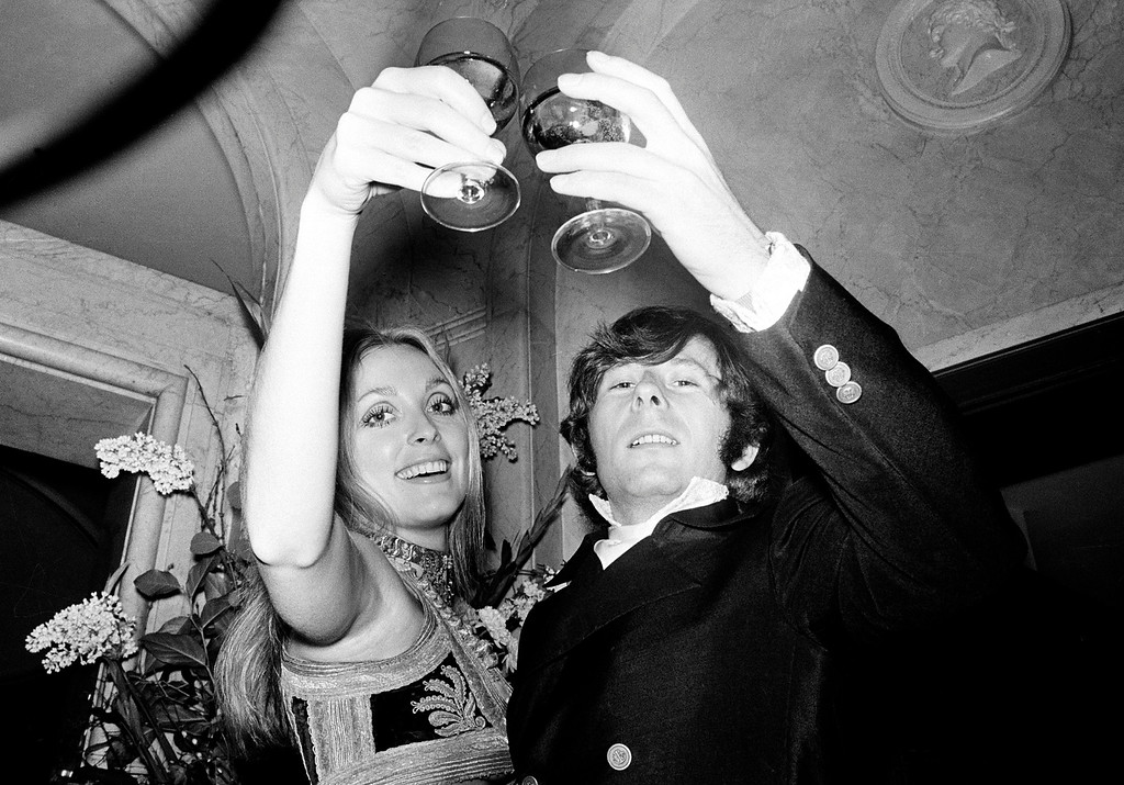 """. Film director Roman Polanski and his wife, actress Sharon Tate, lift their glasses in a toast at the premiere of his film \""""Rosemary\'s Baby\"""" in London, England, Jan. 23, 1969.  (AP Photo)"""