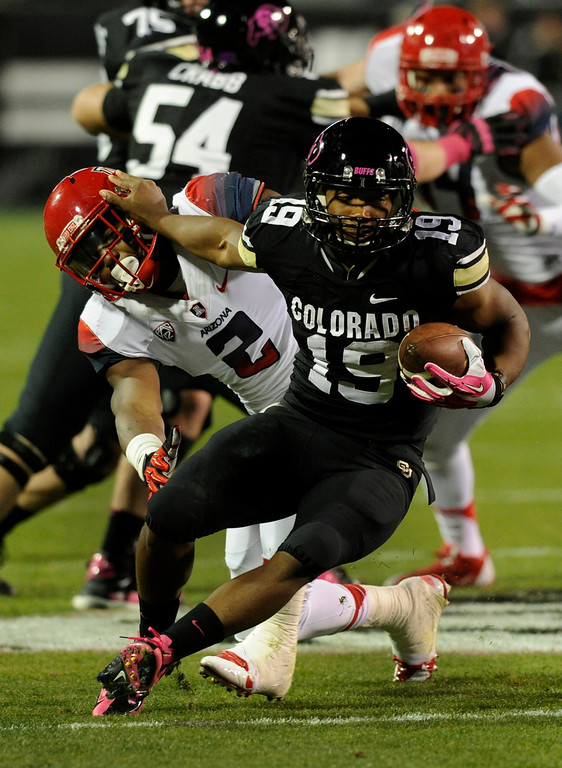 . BOULDER, CO. - OCTOBER 26: Colorado running back Michael Adkins III (19) tried to bounce away from Arizona defender Marquis Flowers (2) in the first half. The University of Colorado football team hosted Arizona Saturday night, October 26, 2013. Photo By Karl Gehring/The Denver Post