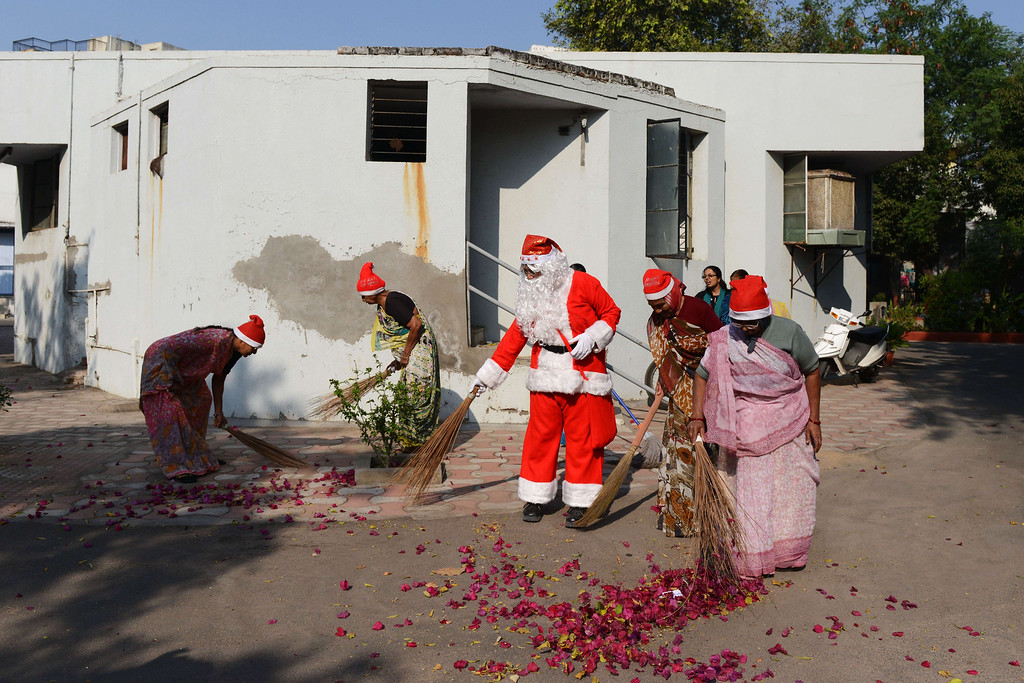 . Indian Harshaben Prajapati (C), dressed as Santa Claus, participates in a cleanliness drive along with residents of the Shreemati Maniben Tribhovandas Matugrah retirement home, in Ahmedabad on December 25, 2014. Despite Christians forming a little over 2 percent of the billion plus population in India, with Hindus comprising the majority, Christmas is celebrated with much fanfare and zeal throughout the country. SAM PANTHAKY/AFP/Getty Images