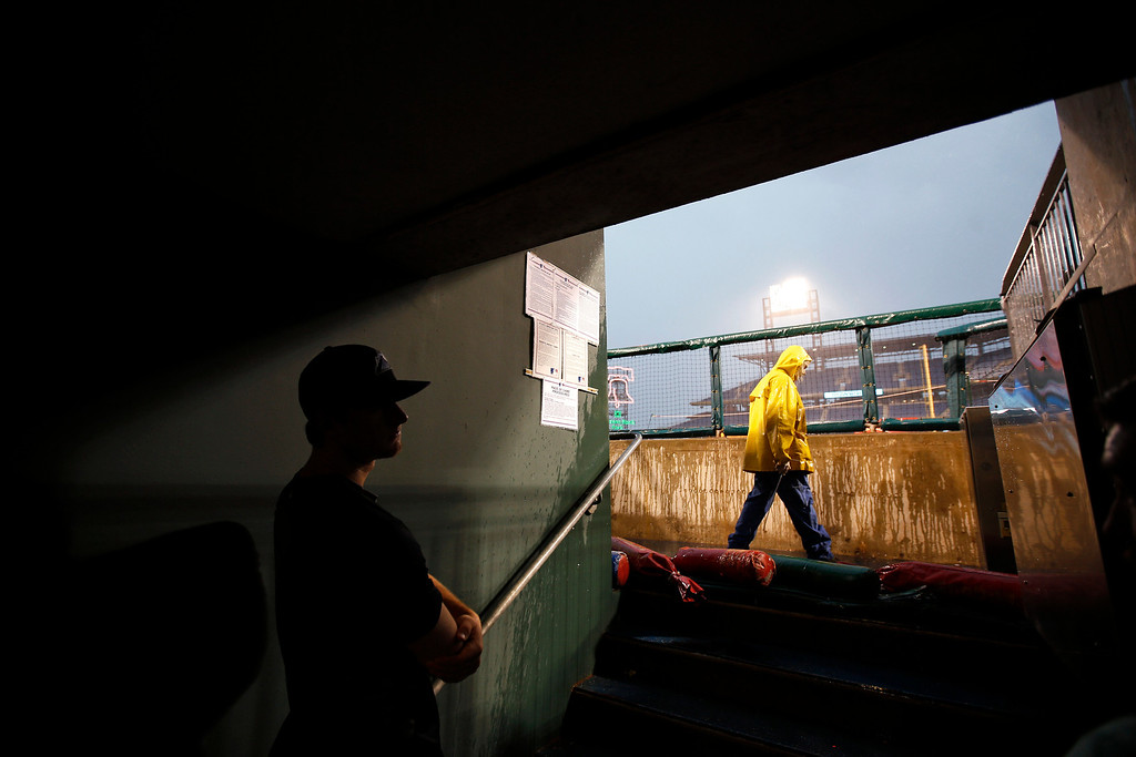 . Colorado Rockies\' DJ LeMahieu looks out from the dugout tunnel during a rain storm before the Rockies\' baseball game against the Philadelphia Phillies, Tuesday, May 27, 2014, in Philadelphia. (AP Photo/Matt Slocum)