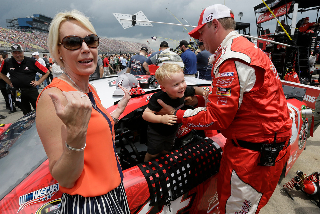 . A crew member pulls out Kevin Harvick\'s son, Keelan Harvick out of the driver\'s seat at DeLana Harvick stands by before the NASCAR Sprint Cup series auto race at Michigan International Speedway, Sunday, June 14, 2015, in Brooklyn, Mich. (AP Photo/Carlos Osorio)