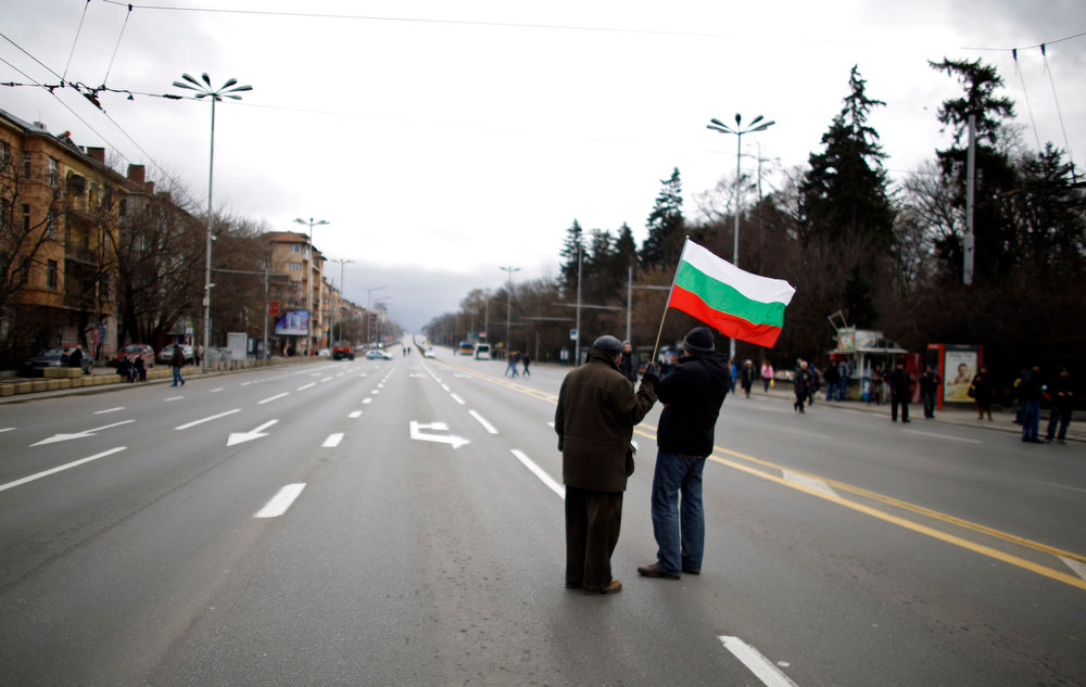 . Demonstrators carry a Bulgarian flag as they arrive for a protest against high utility bills and monopolies in the energy sector in Sofia on February 24, 2013. Tens of thousands of Bulgarians marched through cities across the Balkan country on Sunday, protesting against high utility prices and energy monopolies and demanding sweeping political changes. Public anger with high power bills in the European Union\'s poorest member state forced the rightist government of Boiko Borisov to resign, but the move failed to calm down people, fed up with low living standards and rampant corruption. REUTERS/Stoyan Nenov