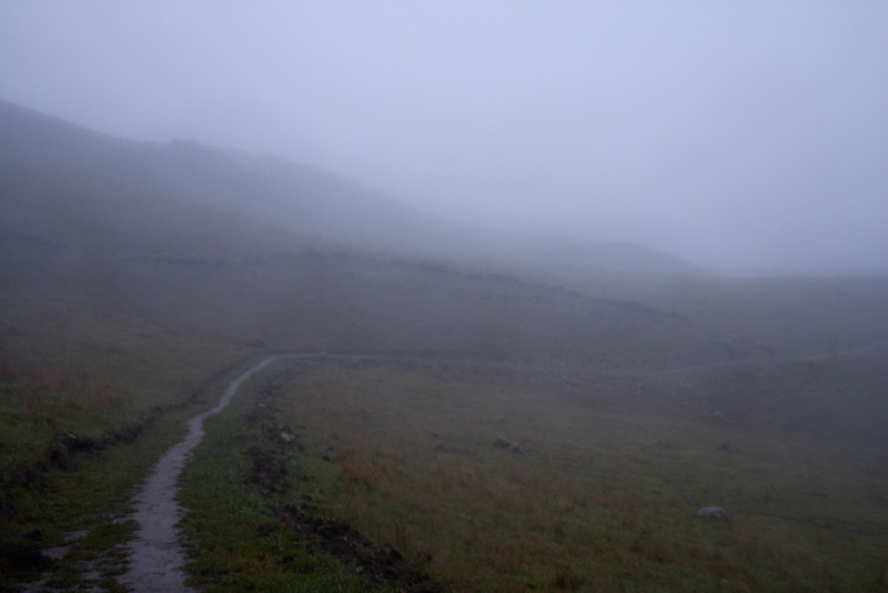 The wet trail fades into the rain and fog.