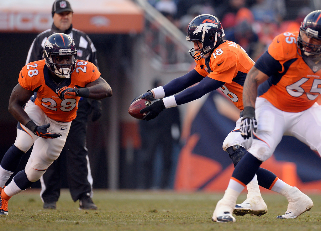 . Denver Broncos quarterback Peyton Manning (18) fakes a hand off to Denver Broncos running back Montee Ball (28) during the first quarter.  The Denver Broncos vs. the San Diego Chargers at Sports Authority Field at Mile High in Denver on December 12, 2013. (Photo by John Leyba/The Denver Post)