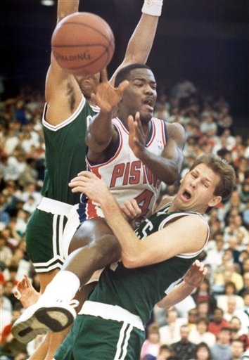 Description of . ** FILE **Detroit's Joe Dumars passes off as he gets caught between Boston's Danny Ainge, right, and Dennis Johnson during the first half of the basketball game at the Silverdome in Pontiac, Mich., Feb. 28, 1988. Dumars is going into the Basketball Hall of Fame Friday, Sept. 8, 2006, and it's fitting that the former Detroit Pistons great will be inducted with the loquacious Charles Barkley and the spectacular Dominique Wilkins. (AP Photo/Duane Burleson, File)
