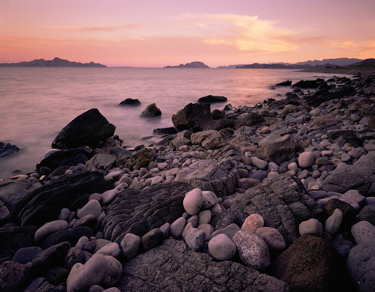 Baja California Sur, Sea, MEX/of Cortez near Loreto. Islands dotting Sea of Cortez with ancient lava and polished stones meeting the sea at sun- set. 290h                      aee