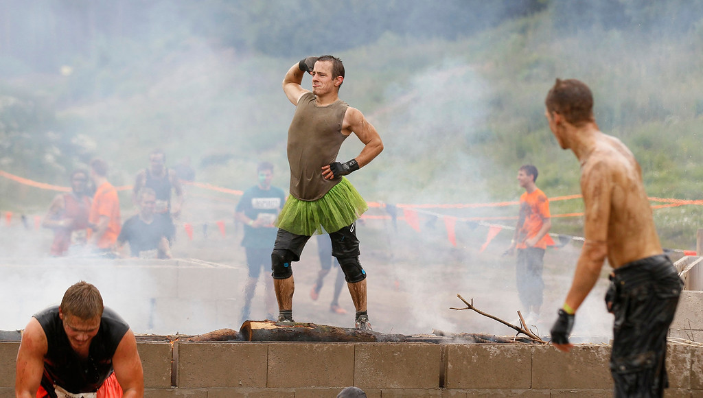 ". A participant of the ""Tough Mudder\"" endurance event series poses on top of an open fire at the \""Fire Walker\"" obstacle in the Fursten Forest, a former British Army training ground near the north-western German city of Osnabrueck July 13, 2013. The hardcore but un-timed event over 16 km (10 miles) was designed by British Special Forces to test mental as well as physical strength. Some 4,000 competitors had to overcome obstacles of common human fears, such as fire, water, electricity and heights.   REUTERS/Wolfgang Rattay"