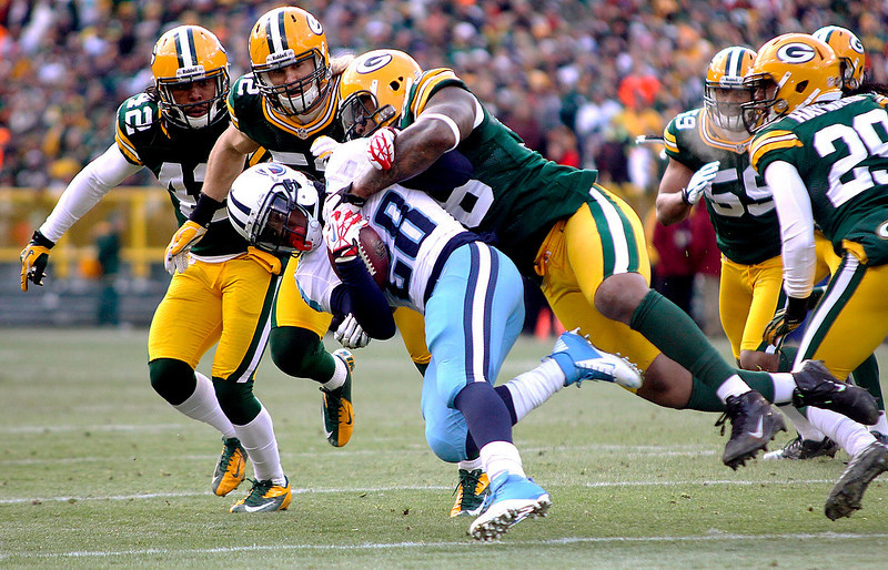 . Green Bay Packers\' Mike Neal (96) tackles Tennessee Titans running back Chris Johnson (28) in the first quarter of an NFL football game at Lambeau Field in Green Bay, Wis., on Sunday, Dec. 23, 2012. Coming in to help Neal are teammates Clay Matthews (52) and  Morgan Burnett (42). The Packers defeated the Titans 55-7. (AP Photo/Shawano Leader, Cory Dellenbach)