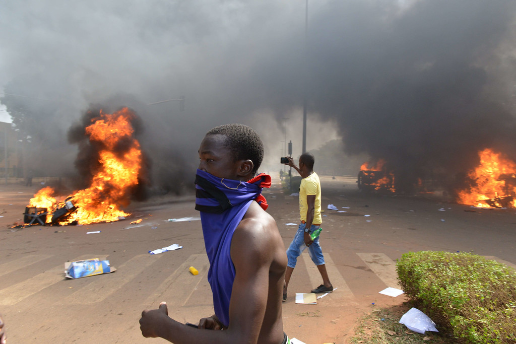 . A protester stands outside the parliament in Ouagadougou on October 30, 2014 as cars and documents burn outside. Hundreds of angry demonstrators in Burkina Faso stormed parliament on October 30 before setting it on fire in protest at plans to change the constitution to allow President Blaise Compaore to extend his 27-year rule. ISSOUF SANOGO/AFP/Getty Images