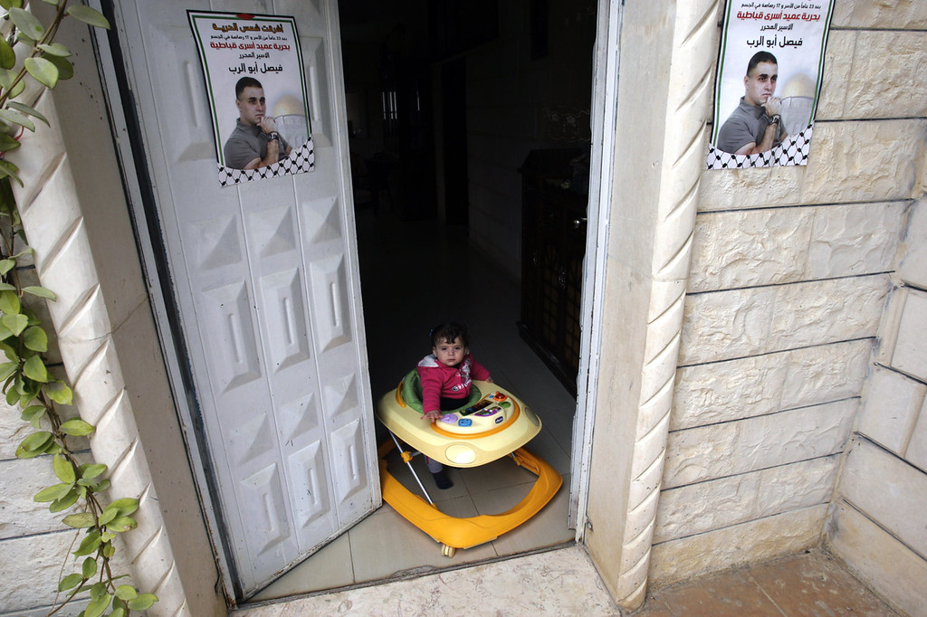 ". A child of a Palestinian relative of Faisal Abo Al-Rob plays at the doorway of their home where Abo Al-Rob\'s posters hang in the West Bank village of Kabatyeh near Jenin city, Sunday, Dec. 29, 2013. Abo Al-Rob is one of the 26 Palestinian prisoners who were convicted in connection to the killing of Israelis, that Israel announced to release this week. The Arabic on the posters reads: ""The freedom Sun rose for releasing Dean of Kabatyeh prisoners, Faisal Abo Al-Rob.\"" (AP Photo/Mohammed Ballas)"