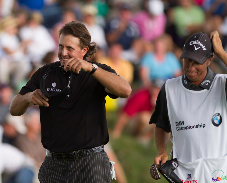 Phil Mickelson is smiling with his caddy Jim McKay after finishing his round during the final round of the 2012 BMW Championship at Crooked Stick Golf Course in Carmel Indiana on Sunday Sept. 9, 2012 (Charles Cherney/WGA)