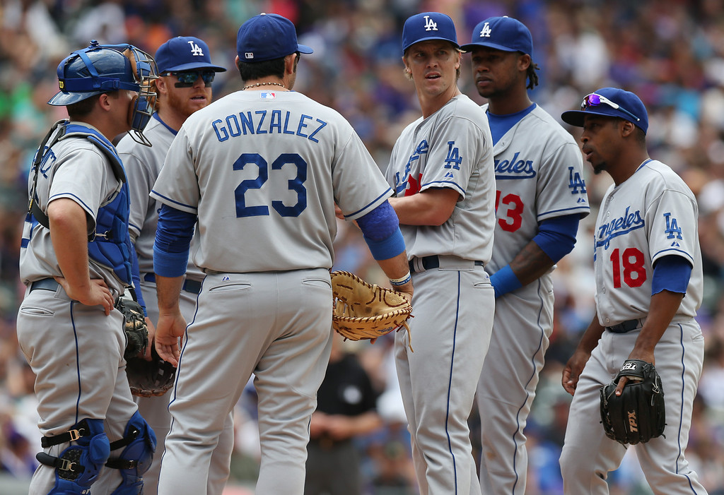 . Los Angeles Dodgers starting pitcher Zack Greinke,  third from right, confers with, from left, catcher Tim Federowicz, third baseman Justin Turner, first baseman Adrian Gonzalez, shortstop Hanley Ramirez and second baseman Chone Figgins after giving up an RBI-single to Colorado Rockies\' Josh Rutledge in the fifth inning of a baseball game in Denver on Saturday, June 7, 2014. (AP Photo/David Zalubowski)