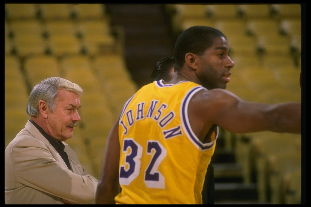 . Guard Earvin (Magic) Johnson of the Los Angeles Lakers looks on with Lakers owner Jerry Boss during a game.