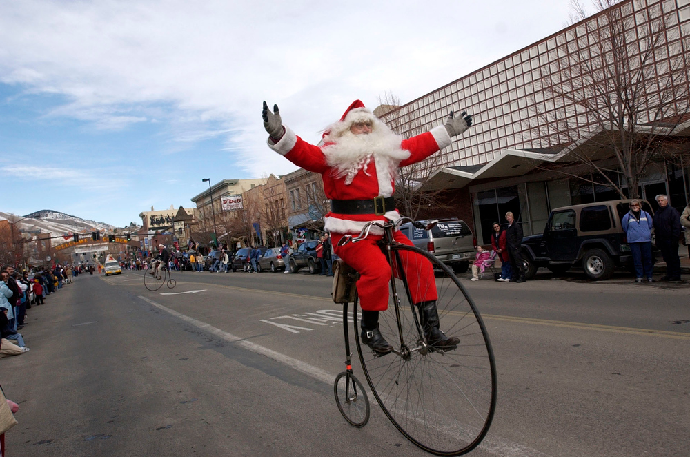 Description of . Steve Stevens of Golden dresses as Santa Claus rides his bike down downtown Golden during their holiday parade through town. Steve belongs to a bike club called The Wheelmen. (DENVER POST PHOTO BY JOHN LEYBA )