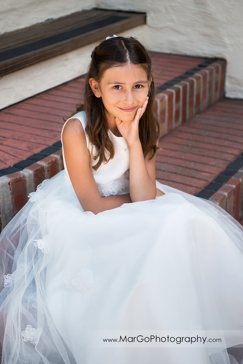 first communion girl in white dress sitting on the stairs at Cafe Wisteria in Menlo Park