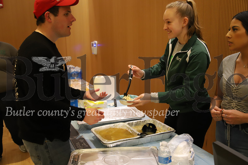 Slippery Rock sophmore Martha Dunkelberger, 19, serves up senior Jake Cribbs, 21, at Friday's Empty Bowls benefit.