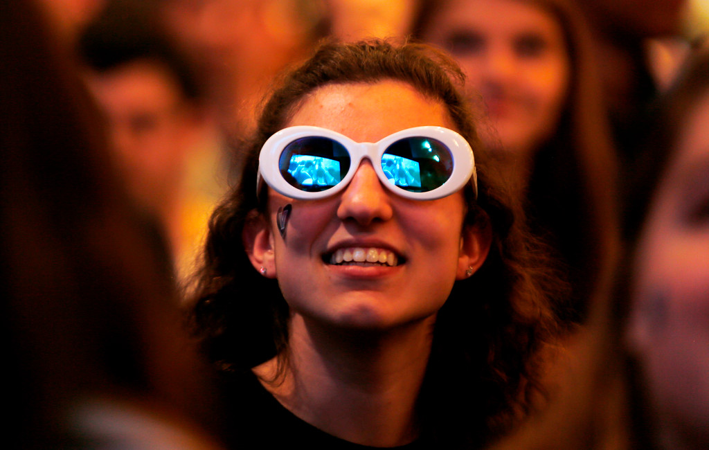 . A wide screen TV is reflected in the glasses of Villanova freshman Gianna Martini as fans cheer ahead of the broadcast of the national NCAA college basketball championship between Villanova and Michigan, Monday, April 2, 2018, in Villanova, Pa. (AP Photo/Laurence Kesterson)