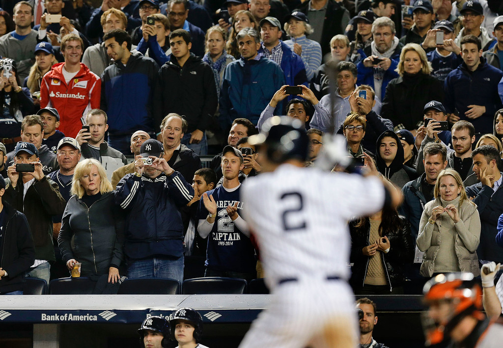 . Fans stand to watch New York Yankees\' Derek Jeter bat against the Baltimore Orioles in the fifth inning of a baseball game, Thursday, Sept. 25, 2014, in New York. (AP Photo/Julie Jacobson)