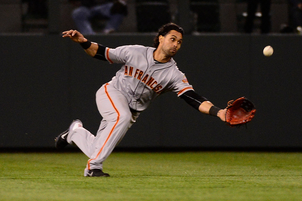. DENVER, CO - APRIL 12: San Francisco Giants left fielder Angel Pagan (16) stretches for a catch off a Colorado Rockies third baseman Nolan Arenado (28) shot to left field during the fifth inning at Coors Field on April 12, 2016 in Denver, Colorado. (Photo by Brent Lewis/The Denver Post)