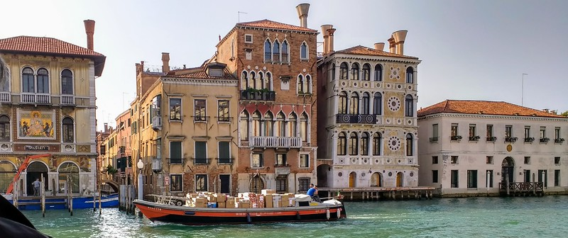 shot of boat floating down venice canal with buildings in the background