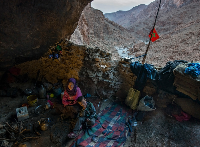 A nomad Berber family sitting inside their cave home.  Todra Gorge, Morocco, 2018.