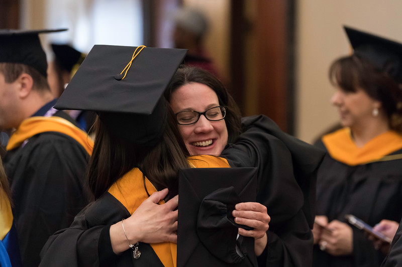 Amy Luce (facing camera) gets a hug from Sarah E. Eichelberger in Lowry Hall before the ceremony. // University of Rochester School of Nursing Commencement, Kodak Hall at Eastman Theatre May 17, 2019.  // photo by J. Adam Fenster / University of Rochester