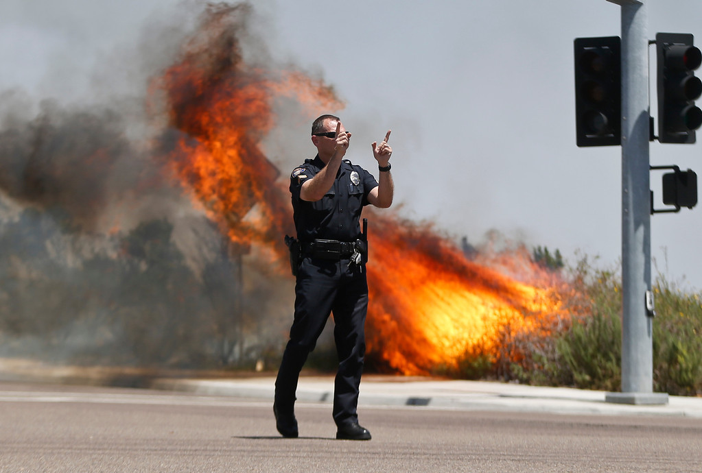 . A Carlsbad,Calif. police officer turns traffic away as flames leap behind him Wednesday, May 14, 2014, in Carlsbad, Calif.  Weather conditions that at least temporarily calmed allowed firefighters to gain ground early Wednesday on a pair of wildfires that forced thousands of residents to leave their homes.  (AP Photo)