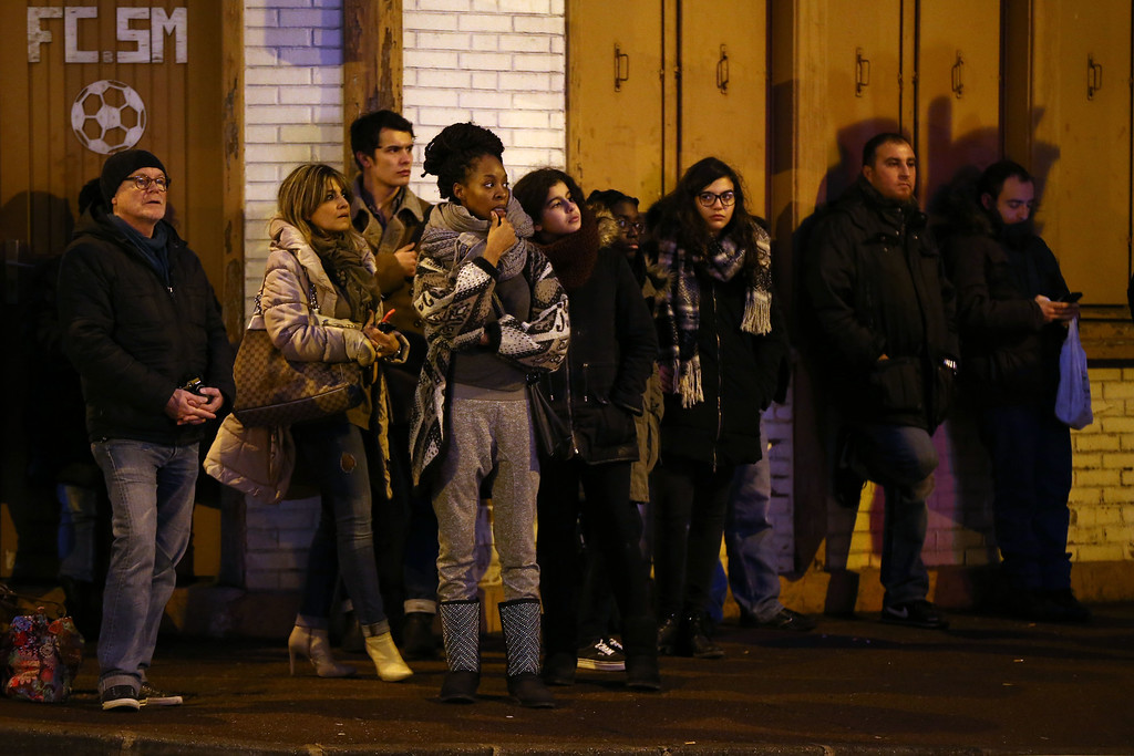 . People watch on Avenue Joffre as police mobilize at the hostage situation at Port de Vincennes on January 9, 2015 in Paris, France. According to reports at least five people have been taken hostage in a kosher deli in the Port de Vincennes area of Paris. A huge manhunt for the two suspected gunmen in Wednesday\'s deadly attack on Charlie Hebdo magazine has entered its third day.  (Photo by Dan Kitwood/Getty Images)