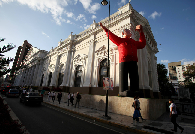 Description of . An inflatable doll depicting Venezuela's President Hugo Chavez sits in front of Venezuela's National Assembly in Caracas, Venezuela, Monday, Feb. 18, 2013. Chavez returned to Venezuela early Monday after more than two months of medical treatment in Cuba following cancer surgery, and was being treated at the Caracas' military hospital, his government said. (AP Photo/Fernando Llano)